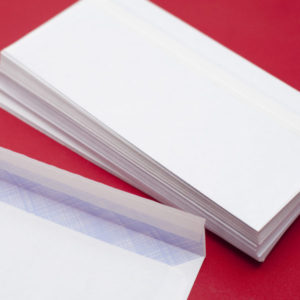Pile of blank white envelopes on a red background waiting to be filled with circulars or correspodence